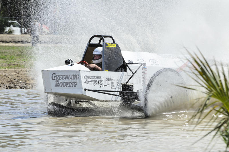 Swamp buggy on straight. Naples, Florida, USA - March 3, 2012: Swamp buggy cranking through straightaway stock image