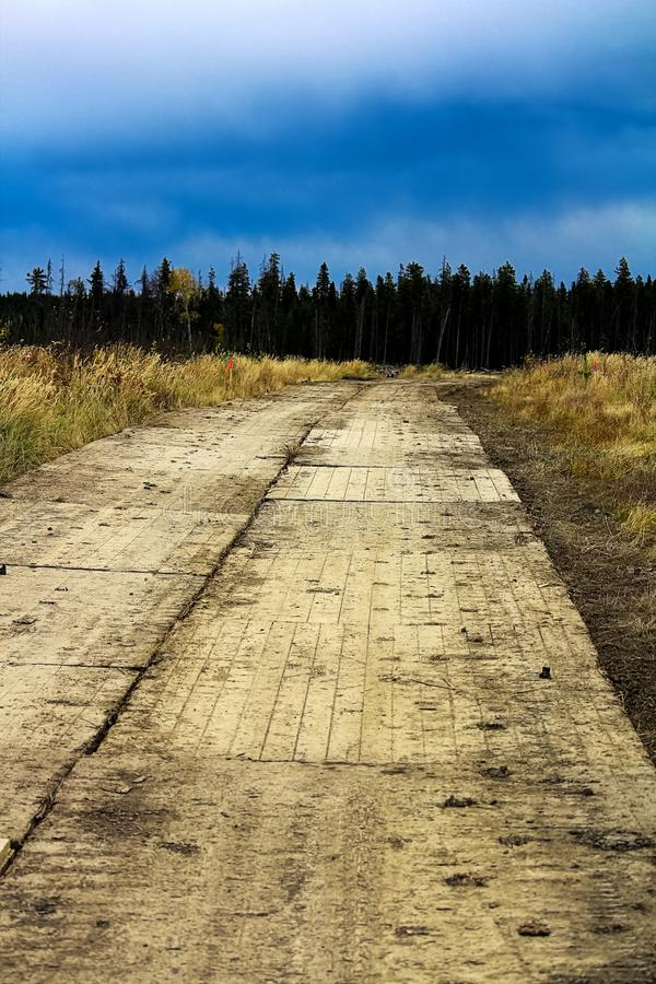 A swamp mat road with a storm approaching in the background.  stock photography