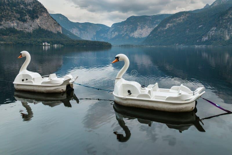 Swan paddle boats moored at Hallstatt lake in Austria stock photography