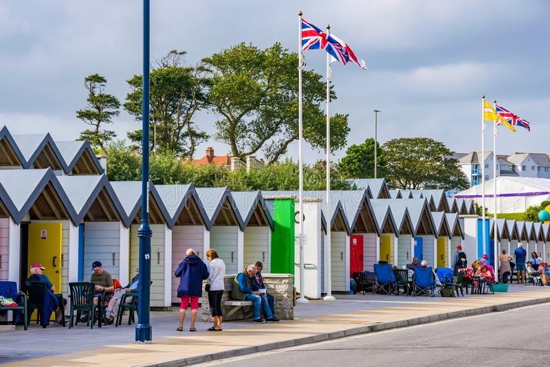 Swanage beach huts. SWANAGE, UNITED KINGDOM - SEPTEMBER 07: This is a view of Swanage beach huts with people relaxing and sitting outside on September 07, 2017 stock images