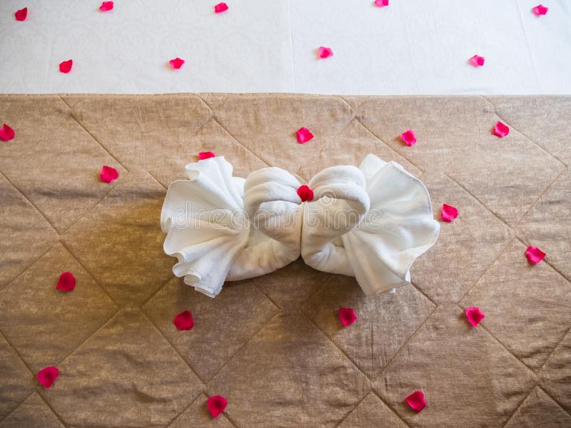 Swans of towels on the bed with rose petals. stock image