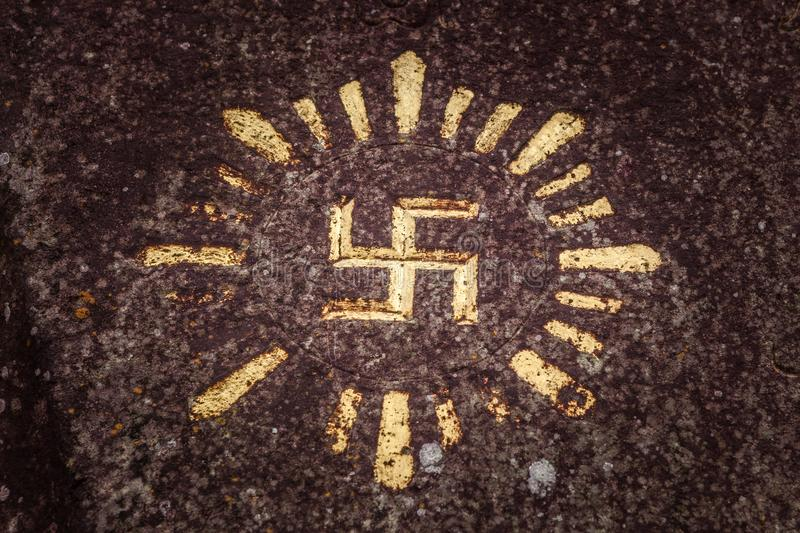 Swastika carved and drawn on a rock - an ancient solar hinduism symbol in the Indonesian culture.  stock photography