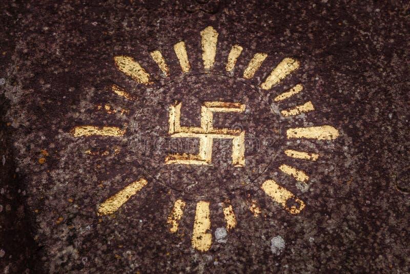 Swastyka rzeźbiąca i rysująca na skale - antyczny słoneczny hinduism symbol w Indonezyjskiej kulturze fotografia stock