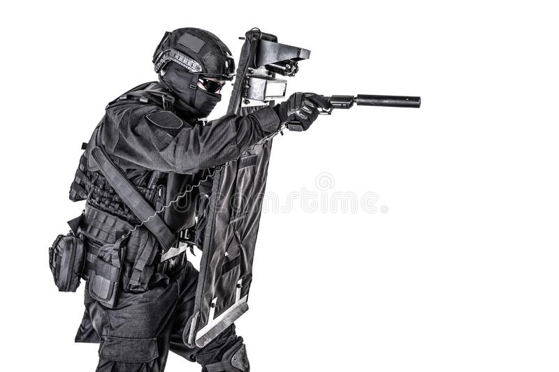 SWAT fighter hiding behind ballistic shield on white. Police special operations and counter-terrorism team, SWAT officer in black uniform, mask and helmet royalty free stock photos
