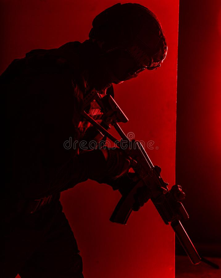 SWAT fighter with silenced assault rifle shoot. Army infantry, special operations forces soldier, police tactical team fighter with suppressed service rifle in royalty free stock images