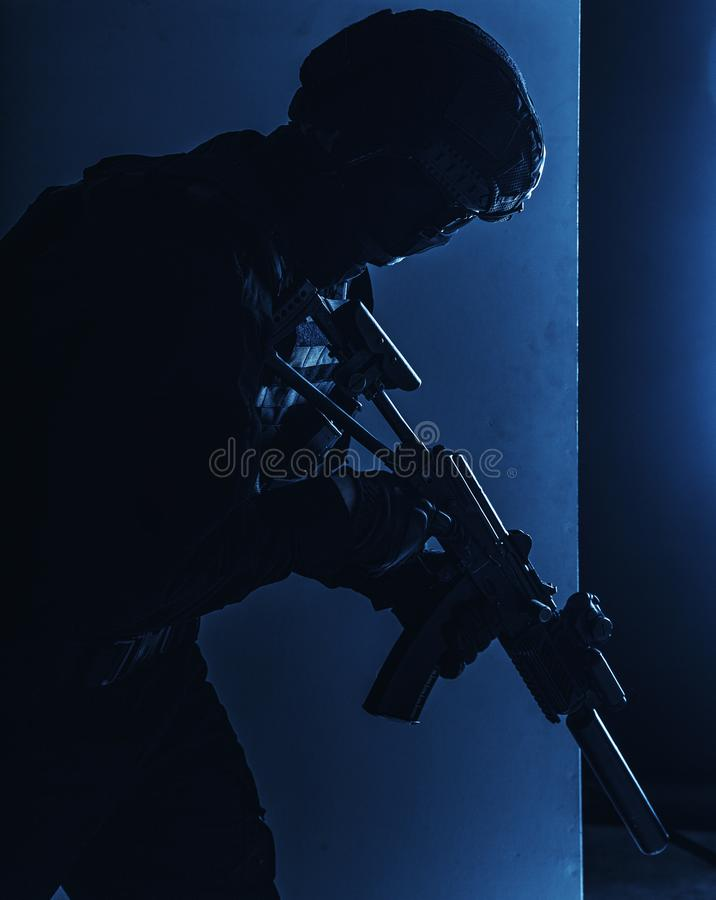 SWAT fighter with silenced assault rifle shoot. Army infantry, special operations forces soldier, police tactical team fighter with suppressed service rifle in stock photos