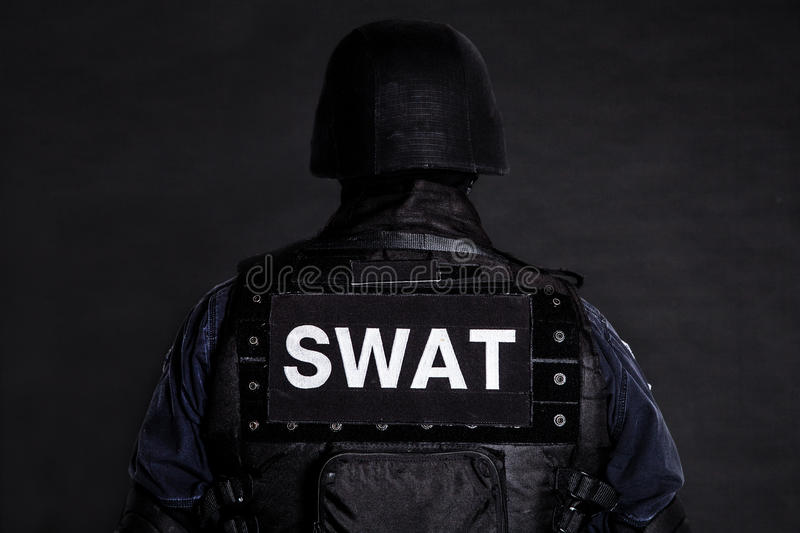 SWAT officer. Special weapons and tactics (SWAT) team officer on black background shot from behind royalty free stock photos