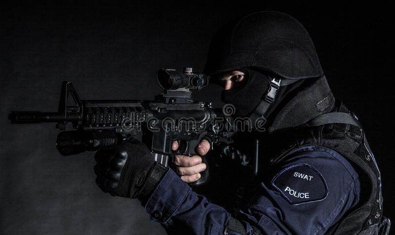 SWAT officer. Special weapons and tactics (SWAT) team officer on black background stock photography
