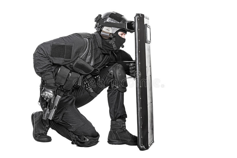 SWAT officer with ballistic shield. Studio shot of swat police special forces with pistol hiding behind ballistic shield. Isolated on white royalty free stock photos
