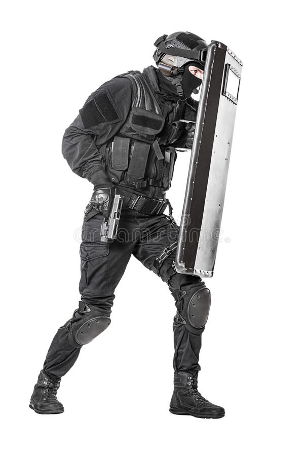SWAT officer with ballistic shield. Studio shot of swat police special forces with pistol hiding behind ballistic shield moving treading. Isolated on white full royalty free stock photography