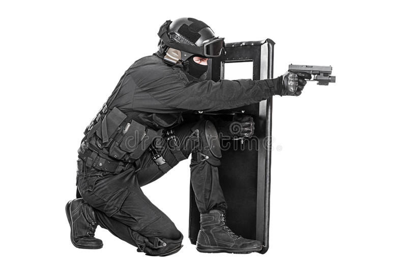 SWAT officer with ballistic shield. Studio shot of swat police special forces aiming criminals with pistol sitting hiding behind ballistic shield. Isolated on stock photos