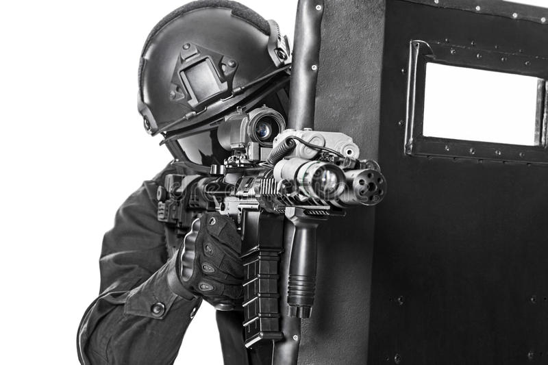 SWAT officer with ballistic shield. Studio shot of swat police special forces aiming criminals with rifle hiding behind ballistic shield. Isolated on white royalty free stock image