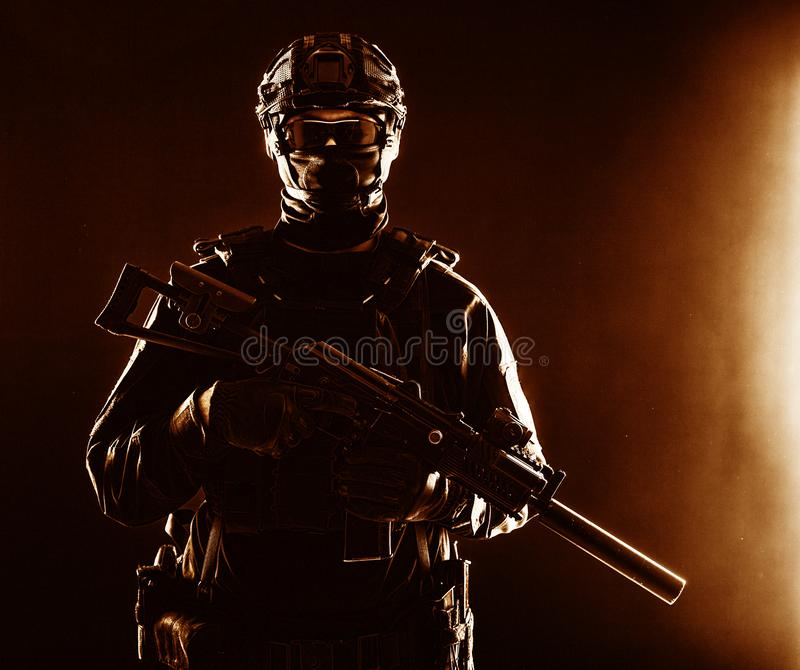 SWAT officer with service rifle low key portrait. Half-length portrait of special forces soldier, army commando, police tactical team or SWAT fighter with hidden royalty free stock photos