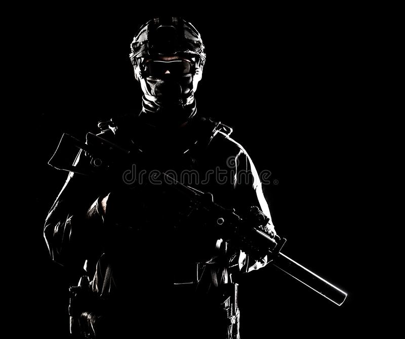 SWAT officer with service rifle low key portrait. Half-length portrait of special forces soldier, army commando, police tactical team or SWAT fighter with hidden royalty free stock image