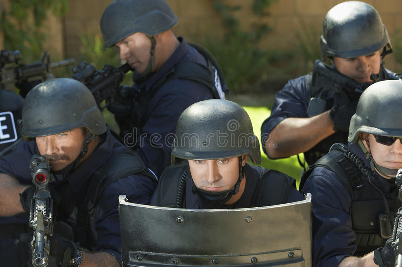 Swat Officers Aiming With Gun Behind Shield stock photos