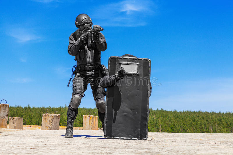 SWAT officers with ballistic shield. Spec ops police officers SWAT with ballistic shield in action stock images