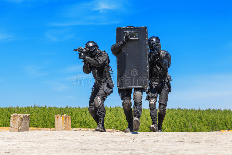 SWAT officers with ballistic shield. Spec ops police officers SWAT with ballistic shield in action royalty free stock photography