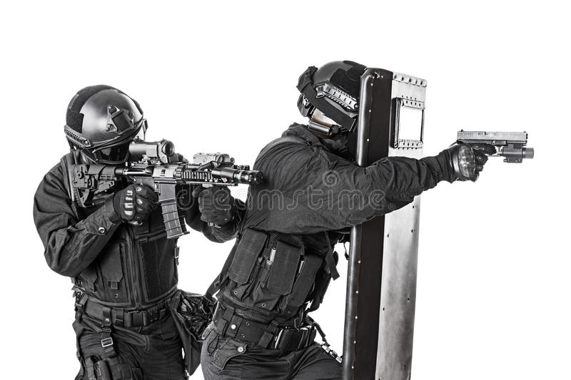 SWAT officers with ballistic shield. Studio shot of swat police special forces aiming criminals with rifle pistol hiding behind ballistic shield. Isolated on royalty free stock image