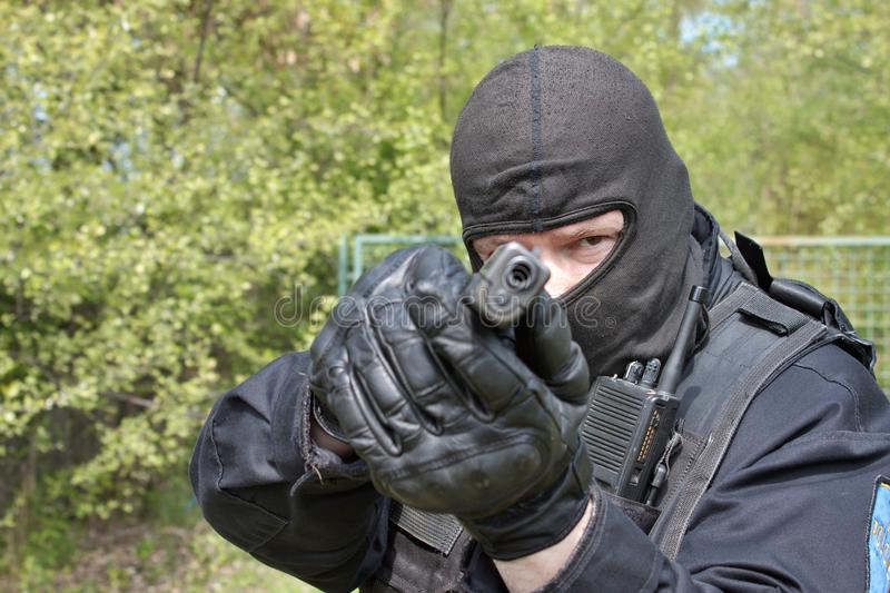 Swat police officer pointing a gun at the camera stock photos