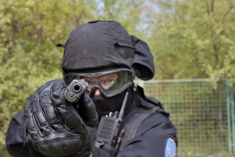 Swat police officer pointing a gun at the camera royalty free stock images