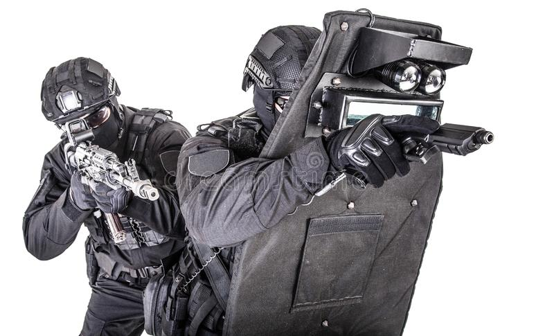 SWAT team behind ballistic shield studio shoot. Two fighters of police quick reaction team, SWAT members, security company shooters aiming with pistol and stock photos