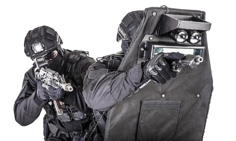 SWAT team behind ballistic shield studio shoot. Two fighters of police quick reaction team, SWAT members, security company shooters aiming with pistol and stock image