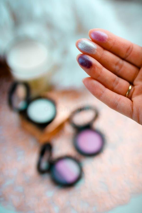 Swatch de sombras de ojos en los fingeres femeninos con el backgroud borroso foto de archivo libre de regalías
