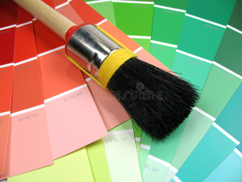 Swatches and brush. A paintbrush lying on some color swatches royalty free stock photo