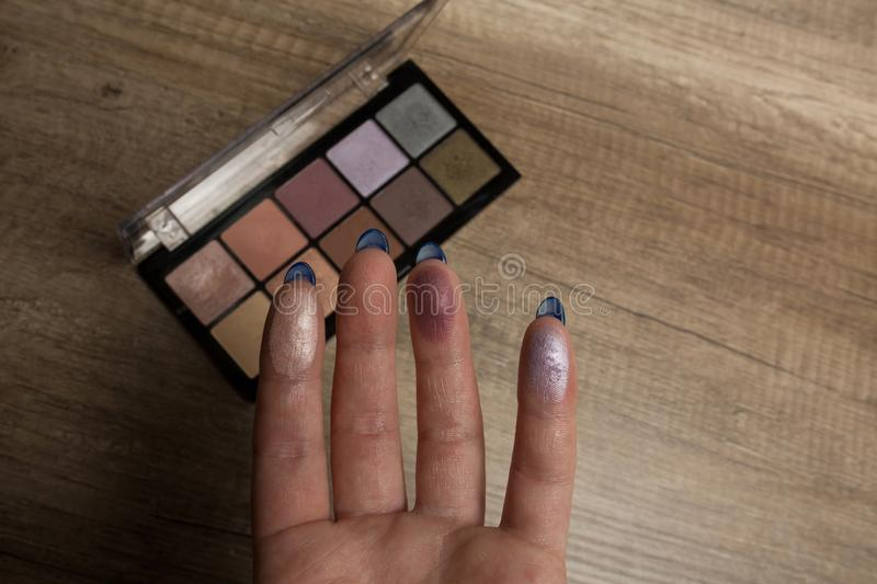 Swatches of palette eyeshadows on a woman`s hand. Wood backgroun. Swatches of shimmer palette eyeshadows on a woman`s fingers. Wood background stock photography