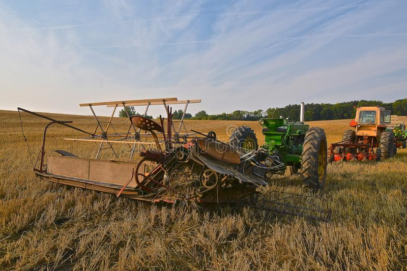 Swathing scene with a John Deere tractor. ROLLAG, MINNESOTA, Sept 1. 2017: A John Deere tractor pulling an old grain swather is ready for demonstrations at the royalty free stock photography
