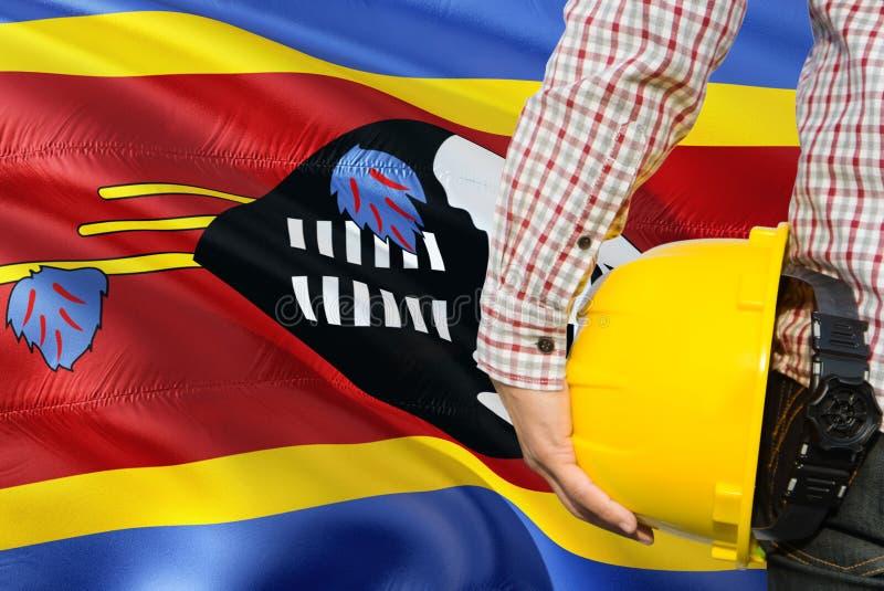 Swazi inżynier trzyma żółtego zbawczego hełm z machać Swaziland chorągwianego tło Budowy i budynku poj?cie zdjęcie stock