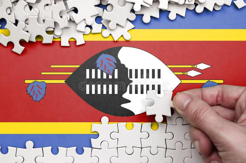 Swaziland flag is depicted on a table on which the human hand folds a puzzle of white color stock photo