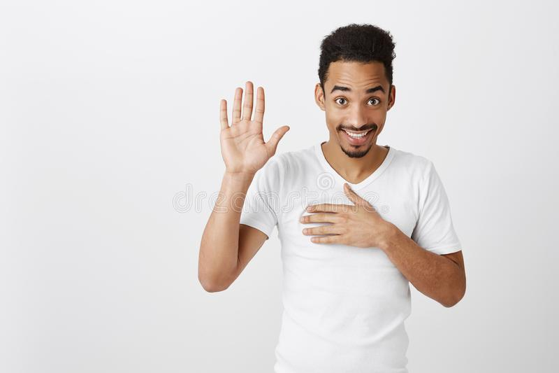 Swear to say truth. Studio shot of sincere happy african-american male with afro haircut, raising palm and holding hand royalty free stock images