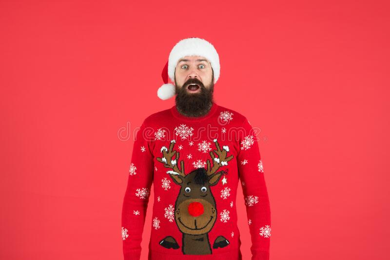 Sweater with deer. Hipster bearded man wear winter sweater and hat red background. Check out my sweater. Happy new year royalty free stock image