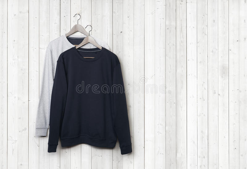 Sweaters on a white wood wall stock images