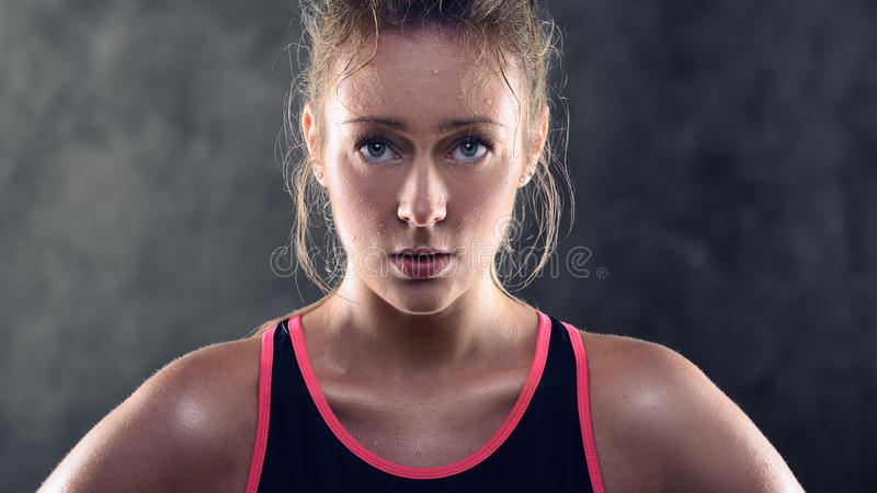 Sweating Athletic Blond Woman Wearing Tank Top. Head and Shoulders Portrait of a sweating Athletic Blond Woman Wearing Pink and Black Tank Top and Standing with stock images