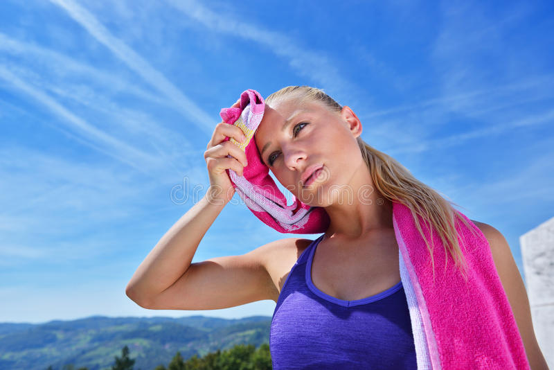 Sweaty fitness woman tired after training. Caucasian female athlete sweating and exhausted after exercising on sky copy space background stock images