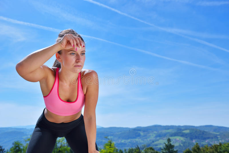 Sweaty fitness woman tired after training. Caucasian female athlete sweating and exhausted after exercising on sky copy space background stock image