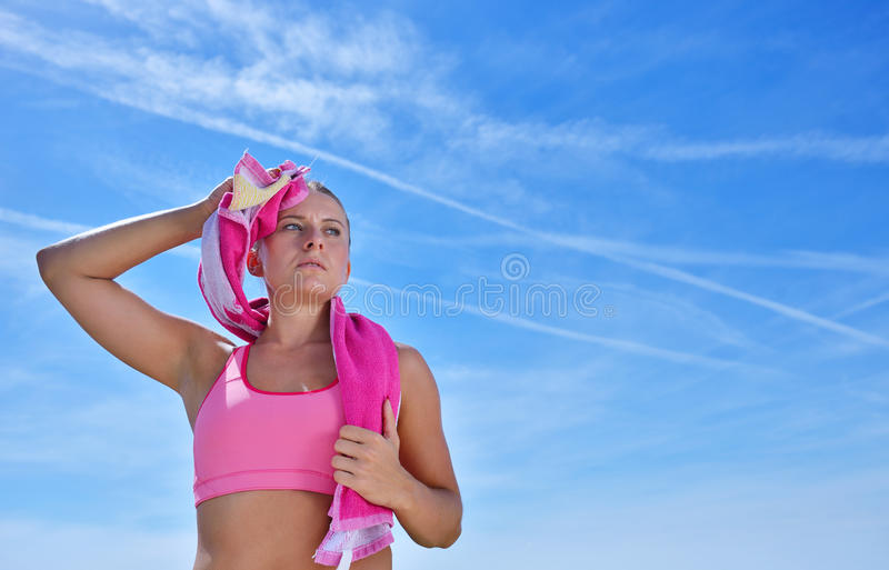 Sweaty fitness woman tired after training. Caucasian female athlete sweating and exhausted after exercising on sky copy space background royalty free stock photography