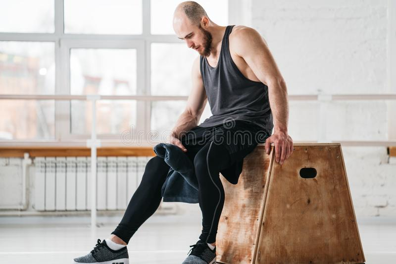 Sweaty muscular man sitting on box in crossfit gym stock photography