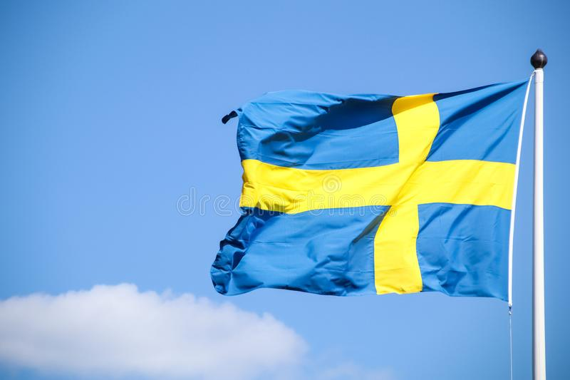 Sweden flag on a pole with beautiful sky background. royalty free stock image