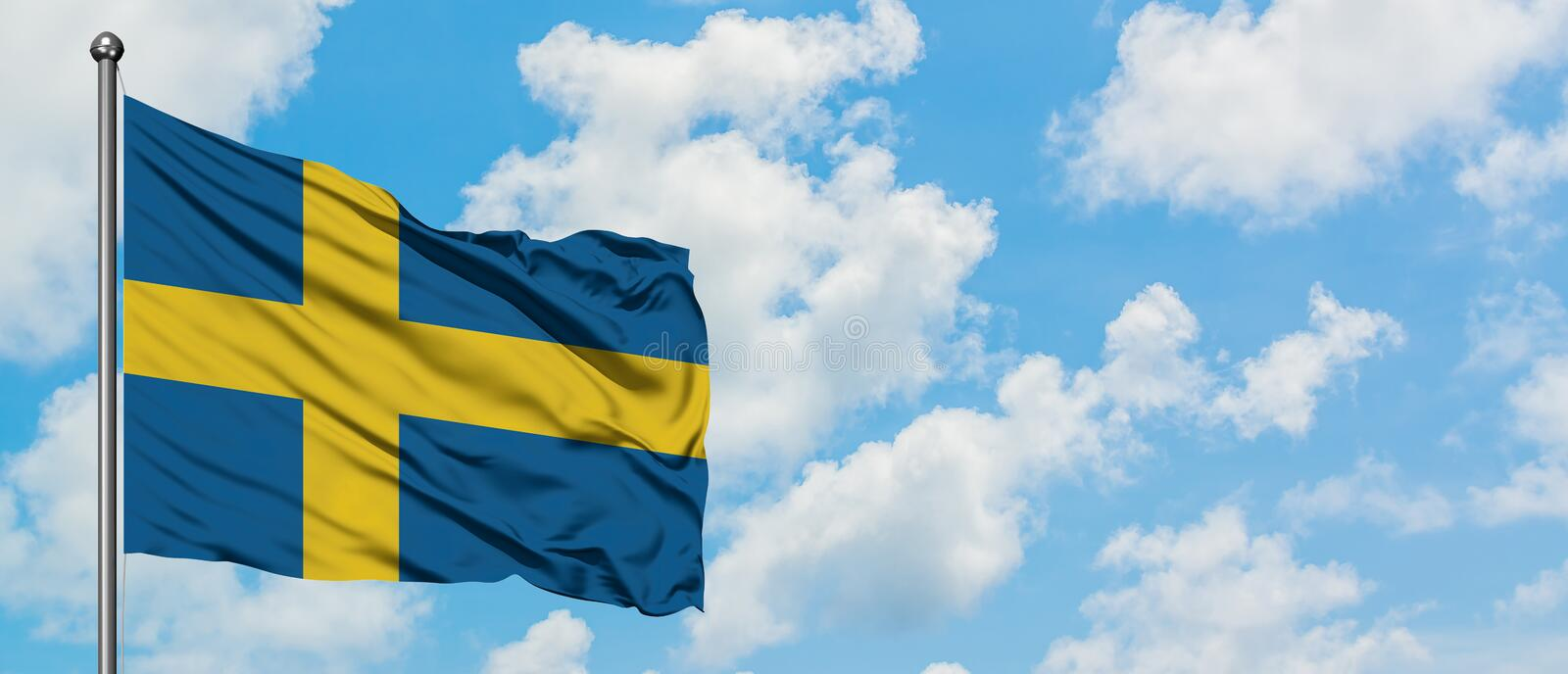 Sweden flag waving in the wind against white cloudy blue sky. Diplomacy concept, international relations.  stock photo