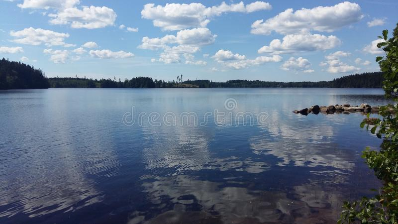 Sweden Lake. Lake in Sweden on a beautiful sunny day with reflections of the clouds on the water. Taken during an outdoor tour in swedish nature royalty free stock photography