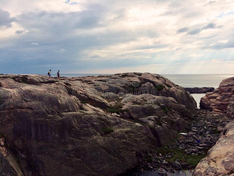 two undefined people walking on a rock by the sea in Sweden stock photography