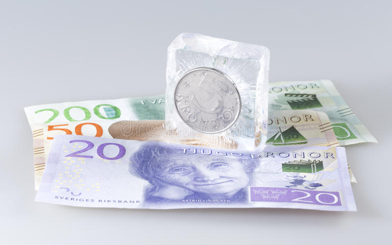 Swedish Five Krona Coin in Ice. On top of notes stock image