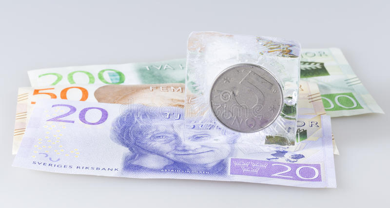 Swedish Five Krona Coin in Ice. On top of notes stock photos