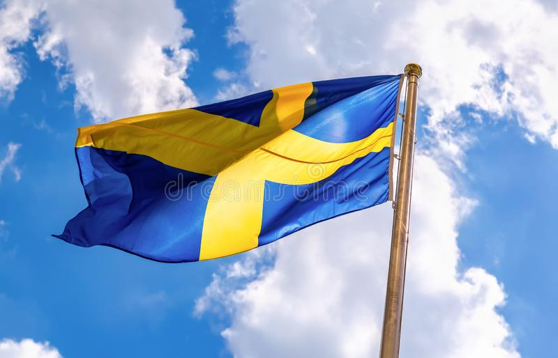 Swedish flag blue with yellow cross waving in the wind. Against a blue sky background with clouds royalty free stock photos