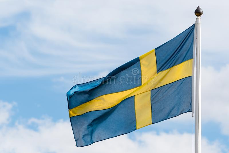 Swedish flag waving in the wind. By a sky with white clouds royalty free stock image