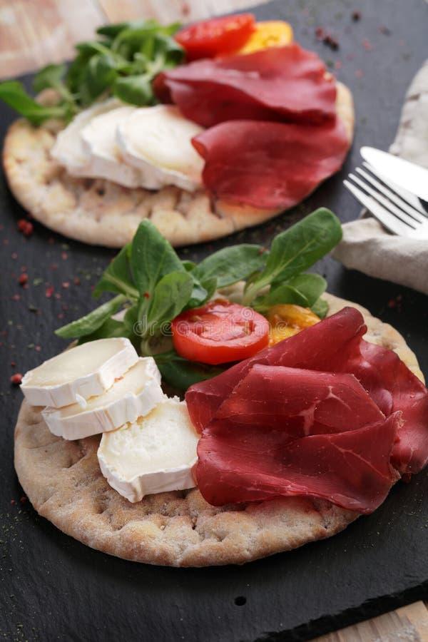 Swedish flatbread hallakaka with ham, cheese, and vegetables royalty free stock image