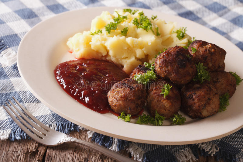 Swedish food: meatballs, lingonberry sauce with potato garnish. Swedish food: meatballs, lingonberry sauce with potato garnish on a plate close-up. horizontal royalty free stock photography